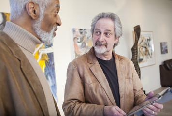 Art gallery curator using digital tablet with customer