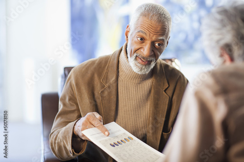 Black man showing paperwork to customer