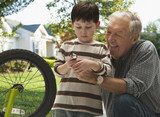Caucasian grandfather and grandson repairing bicycle together