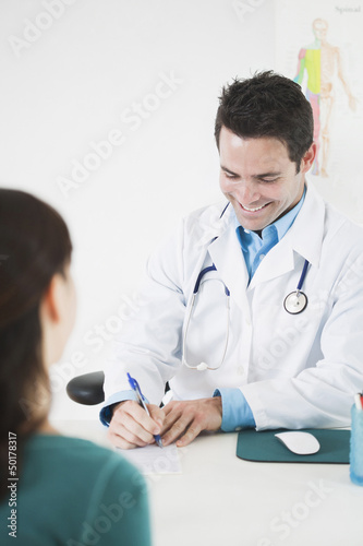 Doctor sitting at desk with patient