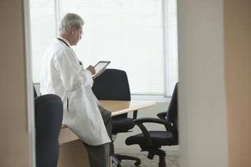 Caucasian doctor using digital tablet in conference room
