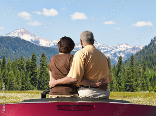 African American couple sitting in convertible looking at mountains