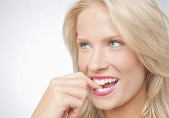 Smiling Caucasian woman biting finger