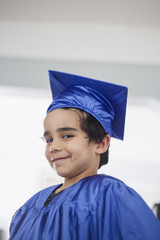 Smiling mixed race boy in graduation cap and gown