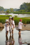 Woman teaching children how to fly fish on river