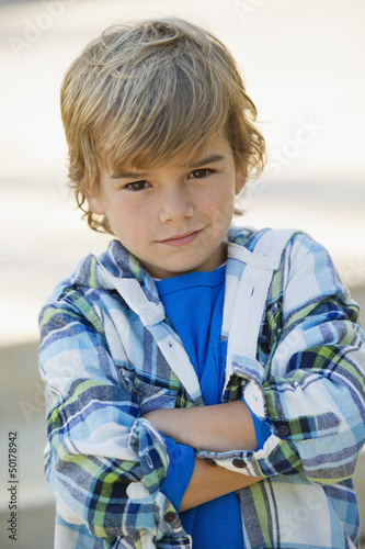 Pouting Caucasian boy with arms crossed