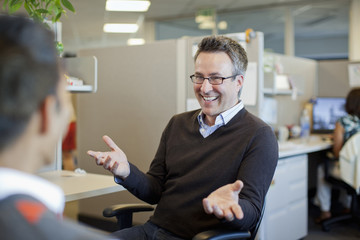 Business people talking in office cubicle