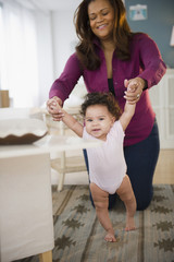 Mixed race woman helping baby learn to walk