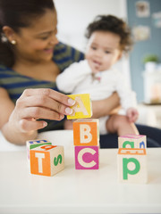 Mixed race mother and baby playing with alphabet blocks
