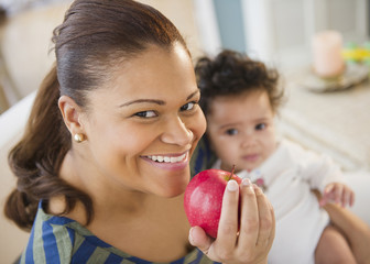 Mixed race mother holding baby and eating apple