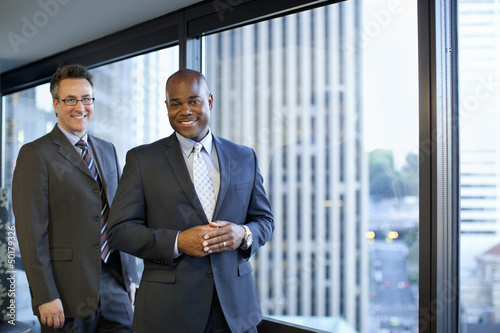 Smiling businessmen standing in office