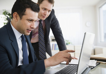 Businessmen working together on laptop
