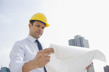 Mixed race businessman looking at blueprints on construction site