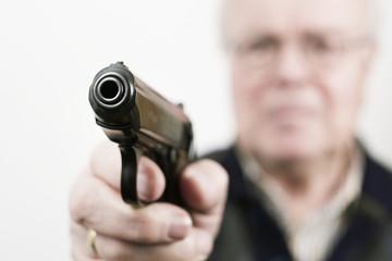 senior mit echter pistole in der hand