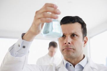 Mixed race scientist holding beaker of liquid