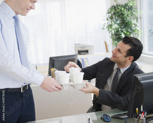 Businessman bringing coffee to co-worker