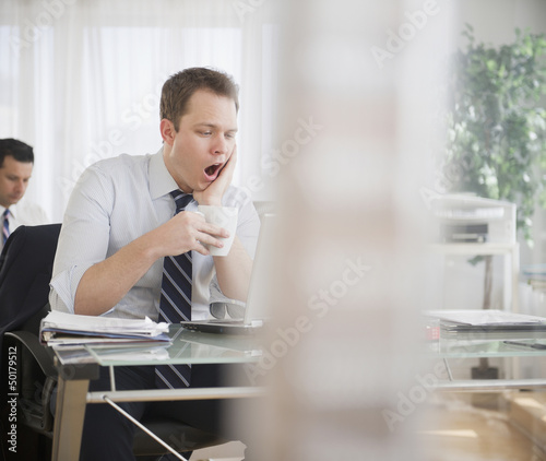 Caucasian businessman drinking coffee and yawning