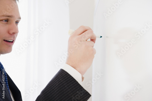 Caucasian businessman writing on whiteboard