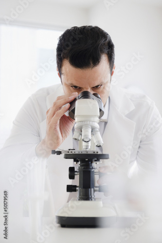 Mixed race scientist looking into microscope