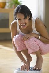 Happy Hispanic woman weighting herself
