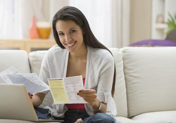 Hispanic woman paying bills online with laptop