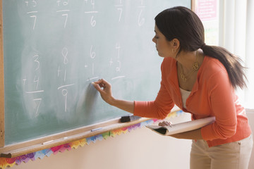 Mixed race teacher writing on blackboard