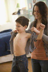 Caucasian mother helping son put on shirt