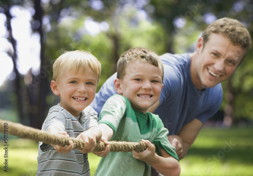 Caucasian father and sons playing tug-of-war