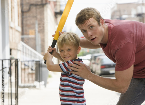 Caucasian father teaching son to play baseball