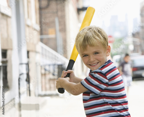 Caucasian boy playing baseball on city sidewalk