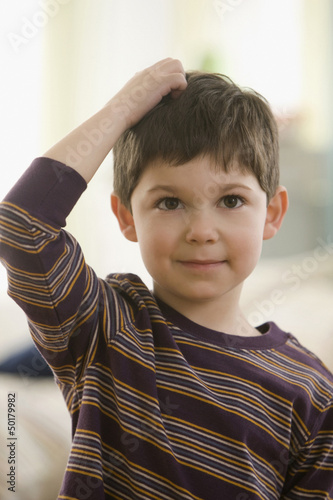 Caucasian boy scratching his head