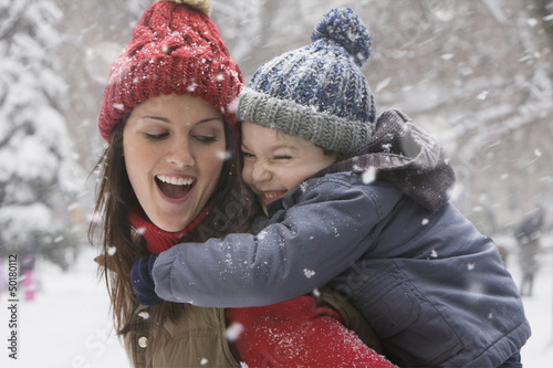 Caucasian mother giving son piggy back ride in snow