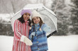 Snow falling on girls underneath umbrella