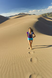 Hispanic woman running on sand dune