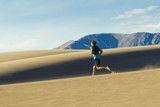 Hispanic man running on sand dune