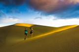 Hispanic couple running on sand dune
