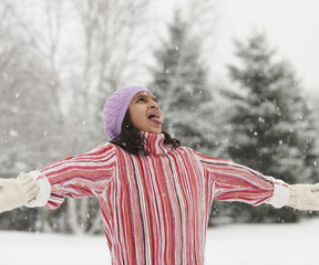 Mixed race girl catching snowflakes on her tongue