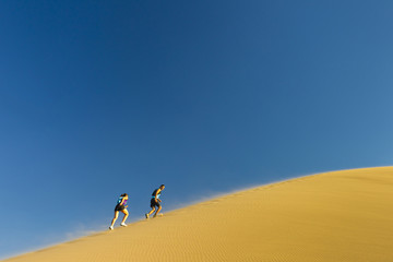 Hispanic couple climbing sand dune
