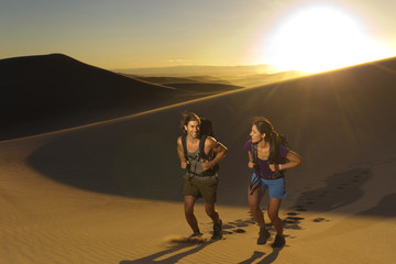 Hispanic couple walking up sand dune