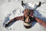 Caucasian woman making snow angel