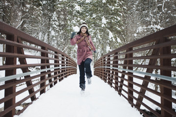 Caucasian woman crossing snow covered bridge