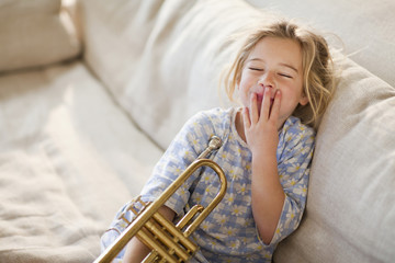 Caucasian girl sitting on sofa with trumpet