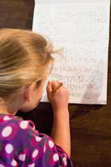 Caucasian girl writing numbers on paper