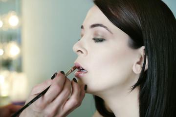 Caucasian woman having makeup put on