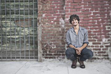 Mixed race man squatting near brick wall
