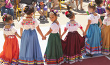 Hispanic girls dancing in costumes