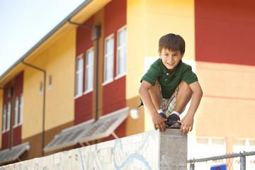 Mixed race boy squatting on wall