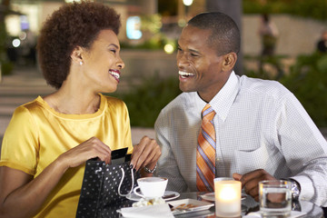 African American giving wife gift over dinner