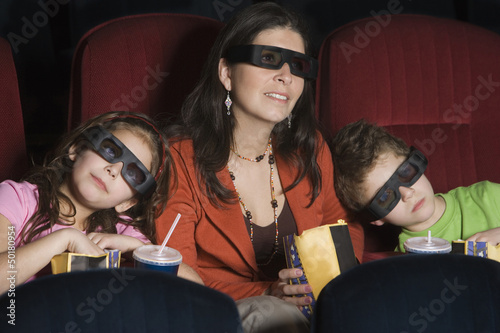 Hispanic mother and children watching 3D movie
