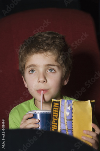 Chilean boy drinking soda in movie theater